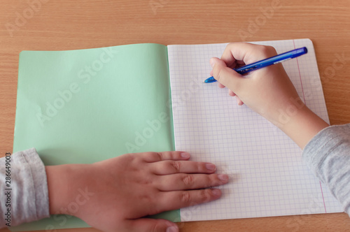 hand of a teenage girl writes with a ballpoint pen in a terad during a lesson at Fototapeta