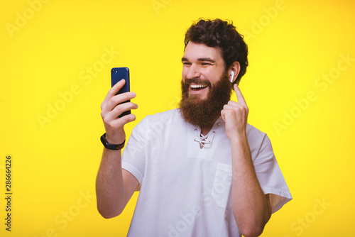 Stampa su Tela Cheerful young bearded hipster trying his new airbuds while looking at his phone on yellow background