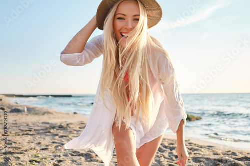 Slika na platnu Young joyful blond woman in swimsuit and white shirt wearing hat while happily l