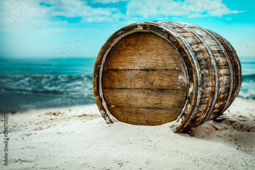 Leinwand Poster Old wooden barrel on the sandy beach with dark blue ocean view.