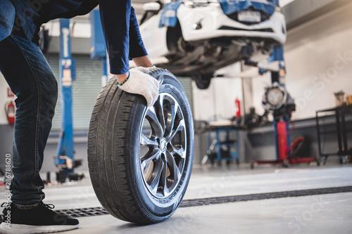 Valokuvatapetti Male mechanic hold and rolling tire at repairing service garage background