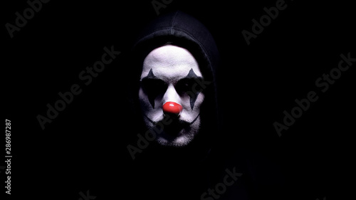 Fotografia Spooky clown in hoodie looking at camera, black background, criminal disguise