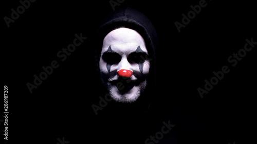 Obraz na płótnie Maniac with spooky clown face angrily smiling into camera, psycho threatening