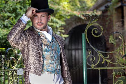 Fotografia, Obraz Portrait of handsome gentleman dressed in vintage costume, holding top hat in st