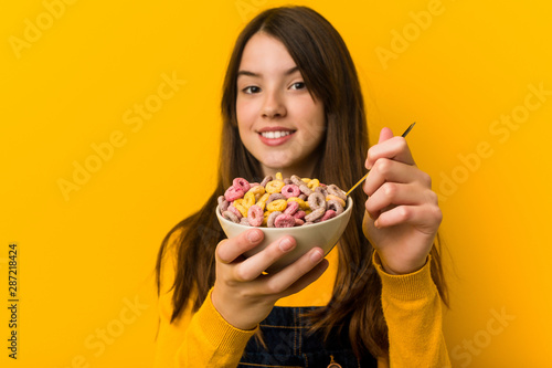 Leinwand Poster Little caucasian girl holding a cereal bowl