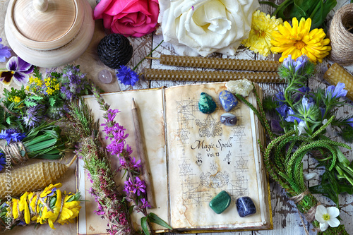 Fototapeta Witch spell book, calendula, rose flowers, reiki crystals and candles on wooden table