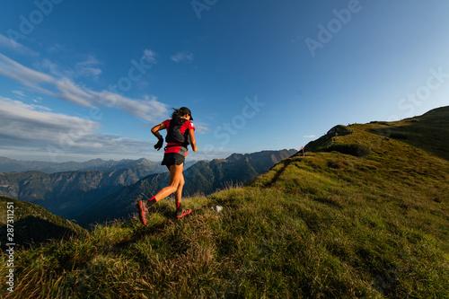 Fototapeta Sporty mountain woman rides in trail during endurance trail