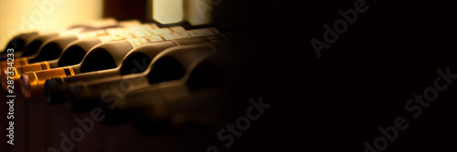 Fotografie, Obraz Bottles of red wine on a wooden shelf, panoramic banner with black background