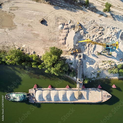 Photo Crane is loading sand and gravel onto barge ship for river transport