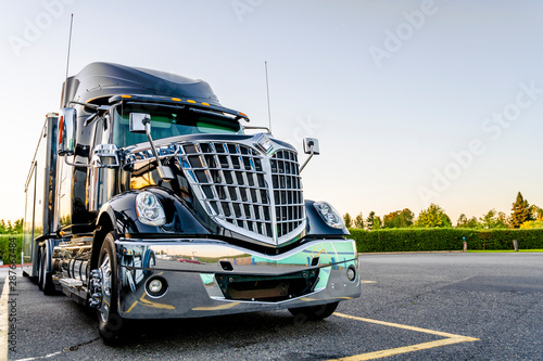 Black stylish big rig semi truck with semi trailer standing in the truck stop parking lot for rest