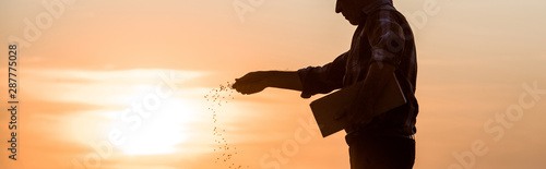 Canvas Print panoramic shot of farmer sowing seeds during sunset