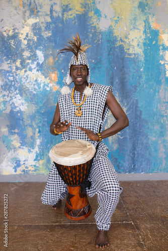 Fototapeta African artist in traditional clothes playing djembe drum