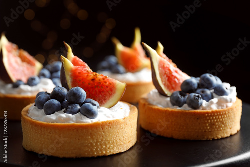Tarts with blueberries and figs on black table against dark background, closeup Fototapeta