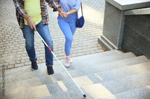 Blind mature man with his daughter walking outdoors Fototapet
