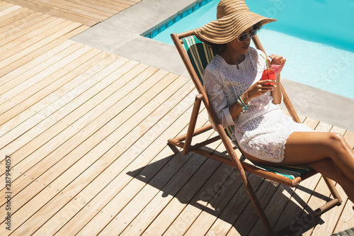 Fototapeta African American woman with cocktail glass relaxing on sun lounger in backyard