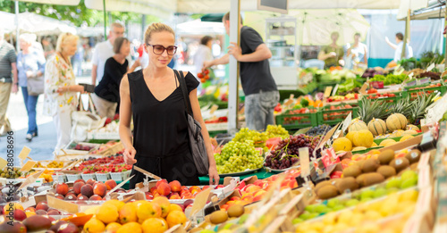 Obraz na plátně Woman buying fruits and vegetables at local food market