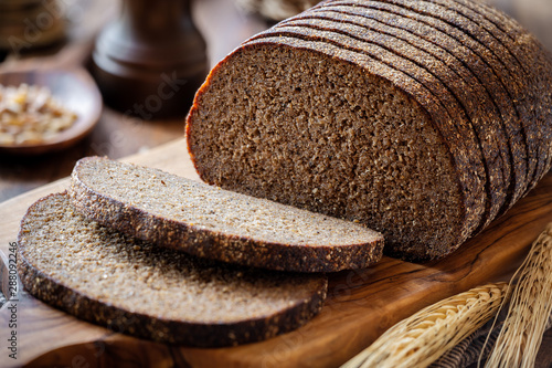 Foto Sliced rye bread on a rustic cutting board with grain and rye ears at the backgr