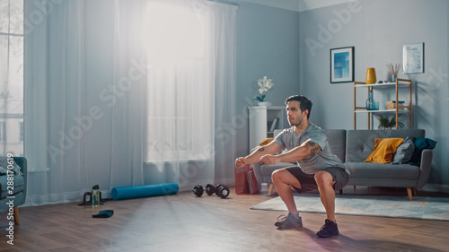 Photographie Muscular Athletic Fit Man in T-shirt and Shorts is Doing Squat Exercises at Home in His Spacious and Bright Living Room with Minimalistic Interior