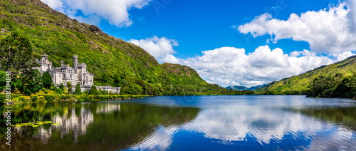 Photo Panorama of Kylemore Abbey, beautiful castle like abbey reflected in lake at the foot of a mountain