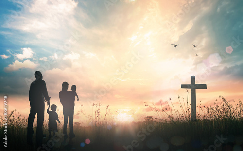 Fototapeta Family worship concept: Silhouette people looking for the cross on autumn sunris