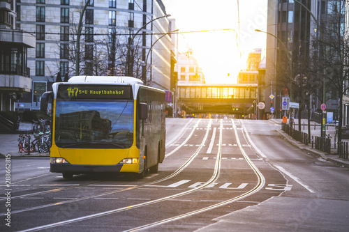Fotografie, Tablou Yellow public transportation bus passing by the city of Berlin Germany