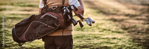 Man carrying golf bag while standing on field