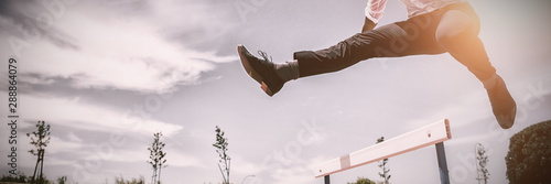 Businessman jumping a hurdle while running