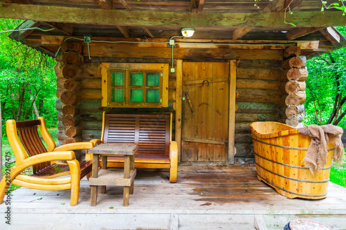 Fotografía The veranda of a small wooden bathhouse on the porch of which there are benches and a large old bath