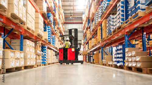 Fotografía Worker in forklift-truck loading packed goods in huge distribution warehouse with high shelves