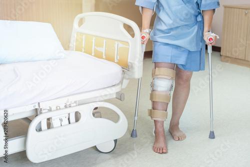 Asian woman patient with knee brace and walking stick in hospital ward after ligament surgery Tapéta, Fotótapéta