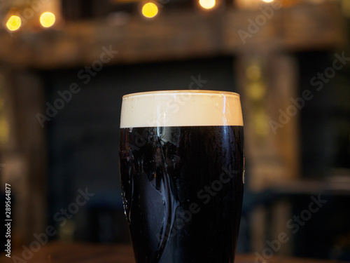 Canvas Print Close-up detail of a glass of cold stout lager in a traditional British pub