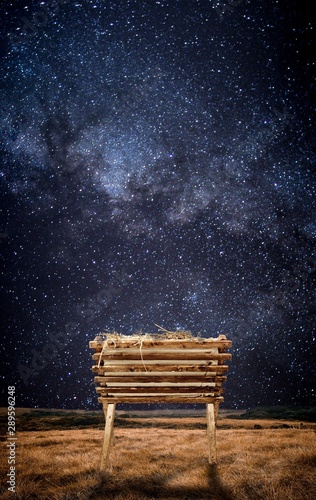 Canvas Print Old wooden cradle with hay in a field and under a starry sky