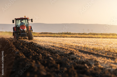 Photo Tractor plowing fields in sunset