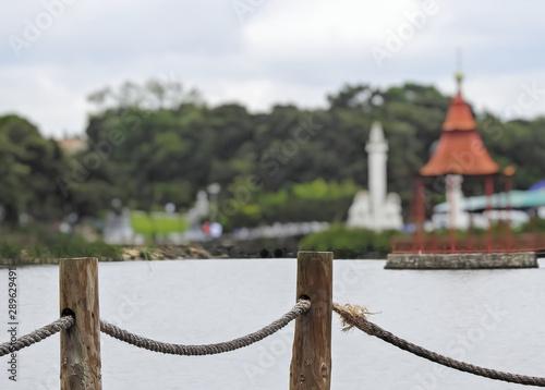 Fototapeta premium Dwa drewniane filary z liną na pierwszym planie