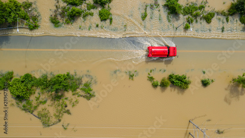 Obraz na plátne Aerial top view of Flooded the village and Country road with a red car, View fro