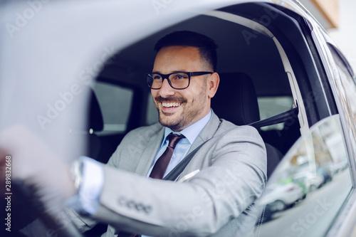 Canvas Print Cheerful caucasian businessman driving himself to work