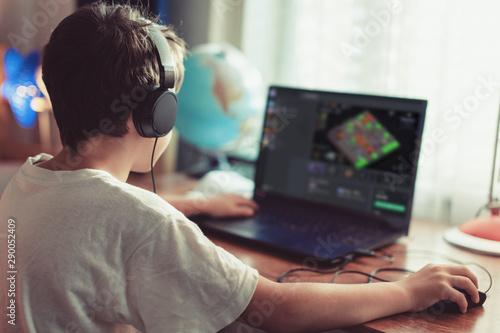 Fototapeta Little dependent gamer kid playing mass multiplayer game on laptop at home