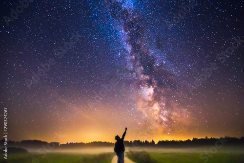 Fototapeta Landscape with Milky way galaxy and man silhuette pointing to the stars