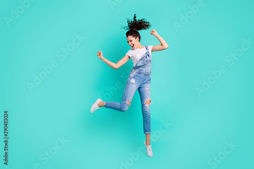 Full length body size view of her she nice attractive lovely cheerful cheery girl wearing blue overall jumping having fun isolated over bright vivid shine vibrant green turquoise background