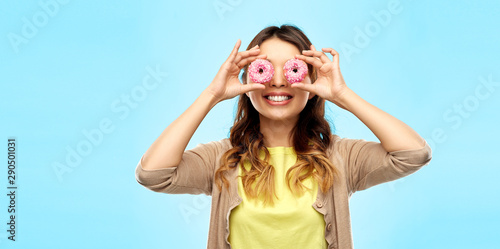 Photo people, fast food and fun concept - happy asian young woman with donuts instead