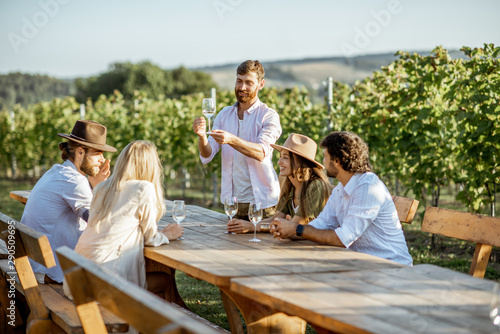 Fotografia Group of a young people drinking wine and talking together while sitting at the