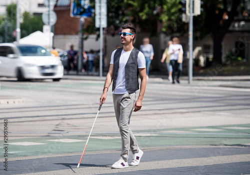 Photo Young blind man with white cane walking across the street in city