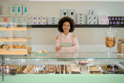 Fotografia Attractive mixed race pastry shop female worker standing next to counter and looking at camera