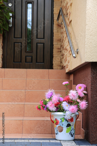 Piękna kolorowa dekoracja z kolorowych kwiatów i wiaderka na schodach domu.