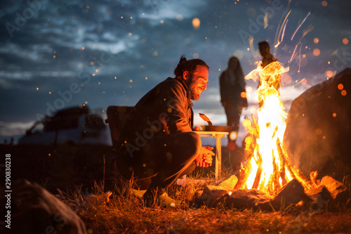 Foto Smiling man next to a bonfire in the dark