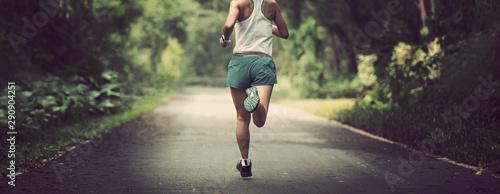 Foto Female runner running at summer park trail