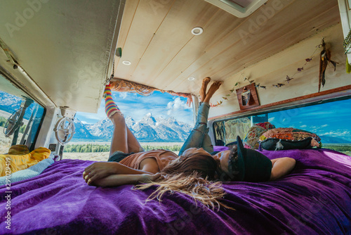 Tela Interior view of a couple relaxing on their bed in a camper van