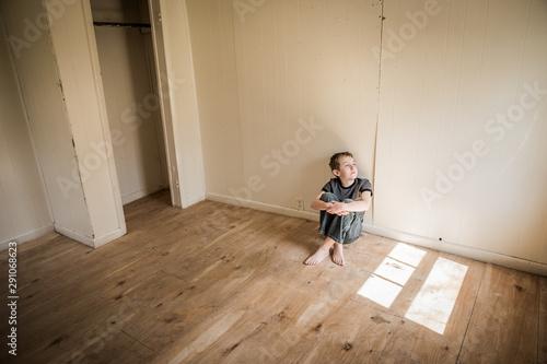 Fotografia Boy sitting alone in an empty room looking out the window