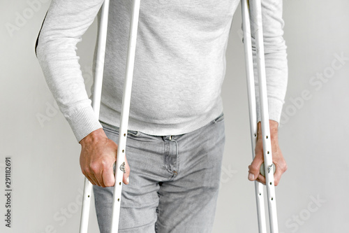 Fotomural Elderly man on crutches on a gray background