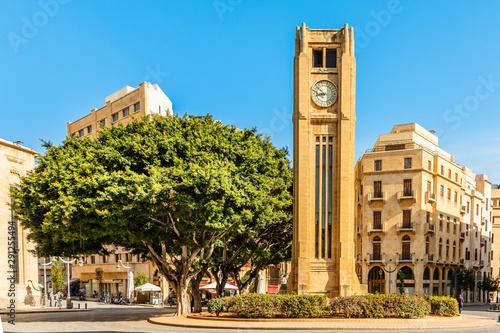 Fototapeta premium Wieża zegarowa na placu Al-Abed Nejmeh z drzewami i budynkami dookoła, Bejrut, Liban